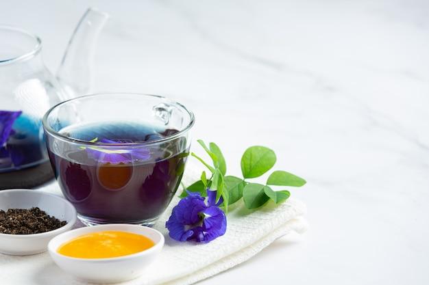 テーブルの上に蜂蜜とバタフライエンドウ豆フラワーティーのカップ 無料写真