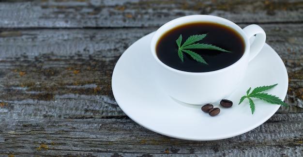 Чашка конопли с листьями конопли и жареных кофейных зерен на деревянный стол Premium Фотографии