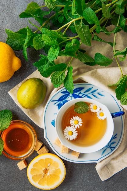 レモン、ブラウンシュガーキューブ、ガラスのボウルと緑の葉の蜂蜜とソーサーにカモミールティーのカップは灰色と布の背景の部分の上に置く 無料写真