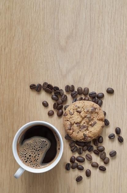 나무 배경에 커피와 초콜릿 칩 쿠키의 컵 프리미엄 사진