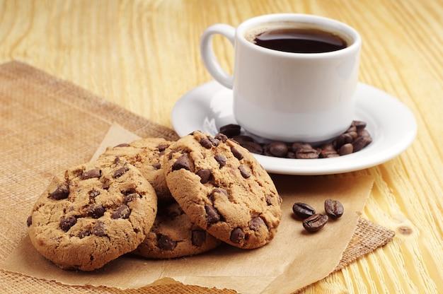テーブルの上のコーヒーとチョコレートクッキーのカップ Premium写真