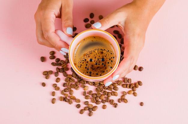 一杯のコーヒーとピンクの表面にコーヒー豆 無料写真