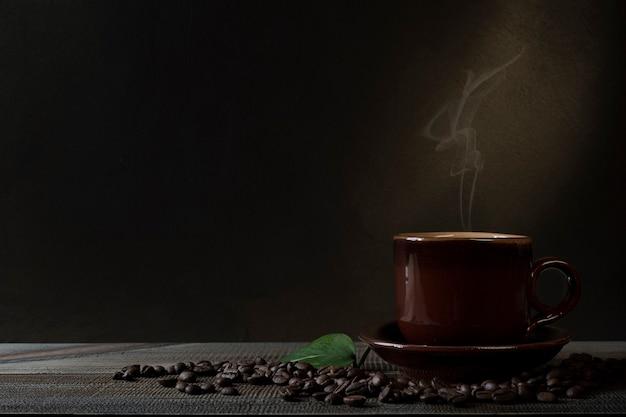 Чашка кофе и кофейных зерен на столе. темный фон. Premium Фотографии