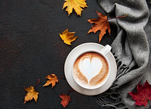 Чашка кофе и сухие листья на черном фоне бетона. Premium Фотографии