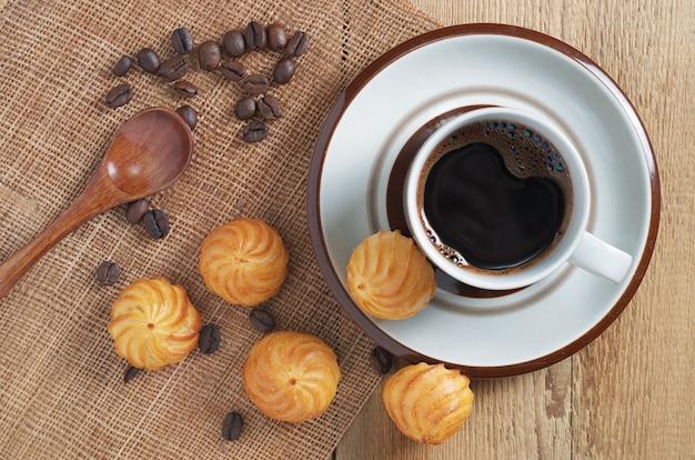 一杯のコーヒーと木製のテーブル、上面に小さなカスタードケーキ Premium写真