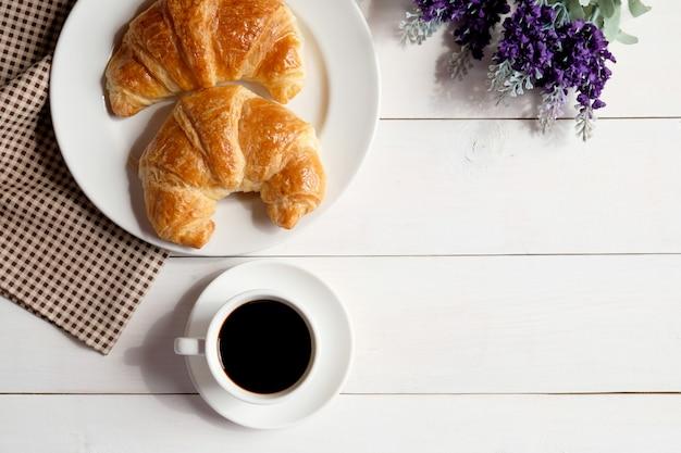 一杯のコーヒーと白い木製の背景にクロワッサンと白い皿。 Premium写真