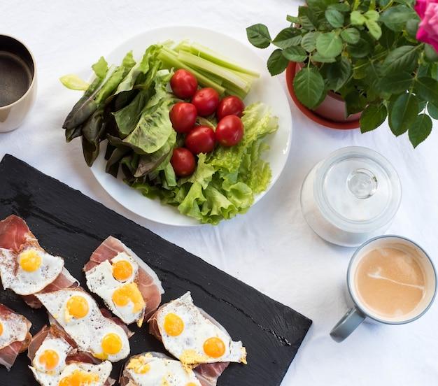 Чашка кофе. брускетта с жареным перепелиным яйцом и пармой. томатный солнечный завтрак. вид сверху Premium Фотографии
