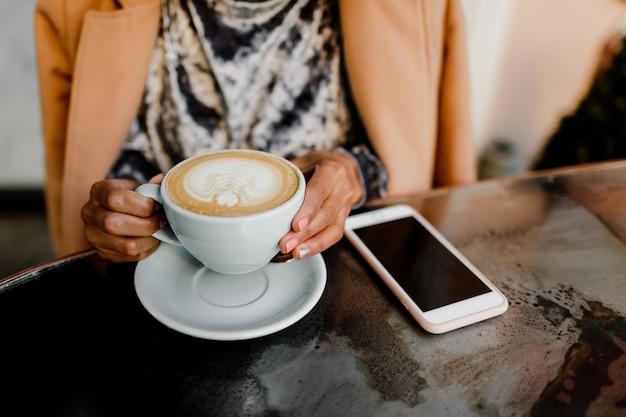 女性の手で一杯のコーヒーカプチーノ。 無料写真