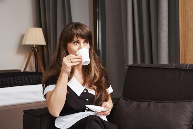 Чашка кофе для домработницы года. портрет мечтательной аккуратной горничной в форме, потягивая чай, глядя в сторону и сидя на диване, смотря телевизор, перерыв в уборке квартиры Бесплатные Фотографии