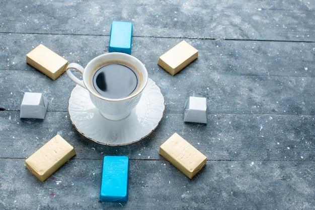水色の机の上に裏打ちされた金の形をしたチョコレートと熱くて強いコーヒーのカップ、コーヒーココアドリンク 無料写真