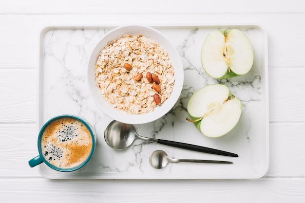 一杯のコーヒー;オートミールとテーブルの上のトレイにスプーンで半分リンゴ 無料写真