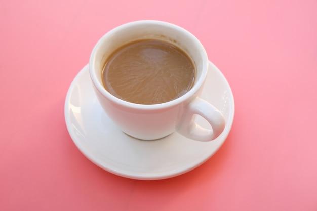 ピンクの背景の上にコーヒーを1杯。 Premium写真