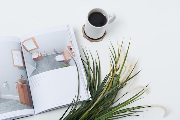 Чашка кофе на столе возле журнала и растений Бесплатные Фотографии
