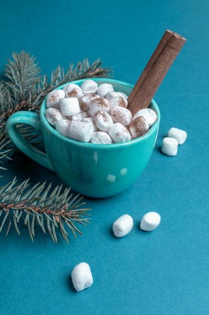Чашка кофе или какао с зефиром и корицей и еловыми ветками на бирюзовой поверхности заделывают. концепция домашнего праздника. рождественское понятие. вертикальная ориентация. Premium Фотографии