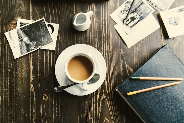 Cup of coffee stands on wooden table among all photos Free Photo
