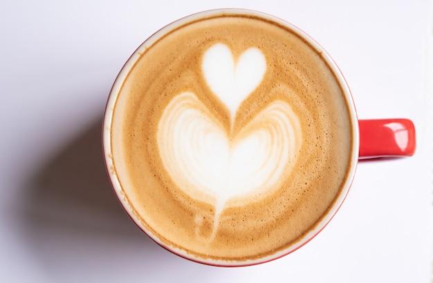 ハート型のバブルとコーヒーのカップは、白い背景にかかっています。 Premium写真