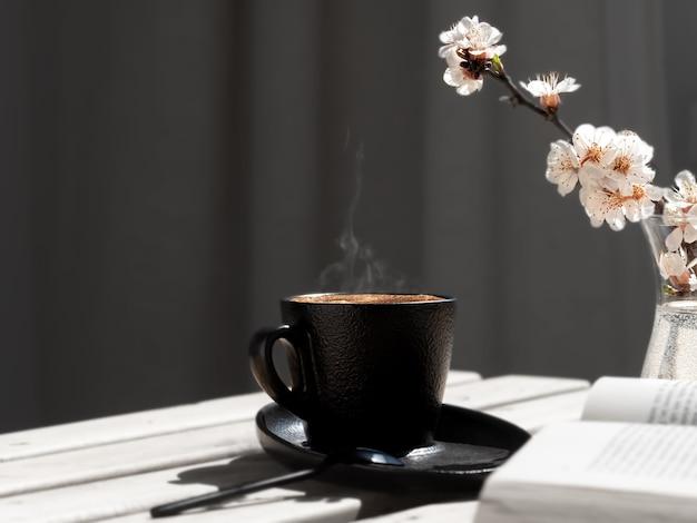 Чашка кофе с ароматным эспрессо на деревянном столе, рядом с открытой книгой и веткой цветущей сакуры Premium Фотографии