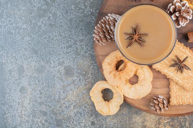 Чашка кофе с палочками корицы и шишками на деревянной тарелке. фото высокого качества Бесплатные Фотографии