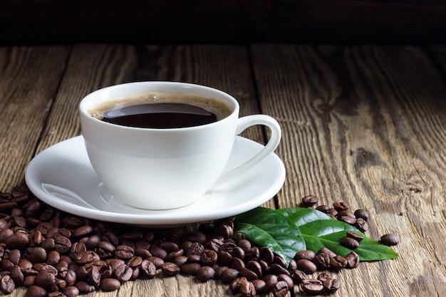 Чашка кофе с кофейными зернами на деревянных фоне Premium Фотографии