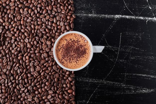 Чашка кофе с зернами вокруг. Бесплатные Фотографии