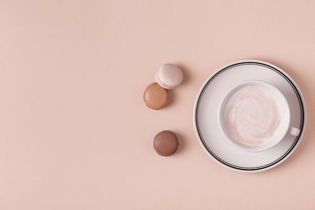 パステル背景にマカロンとコーヒーのカップ Premium写真