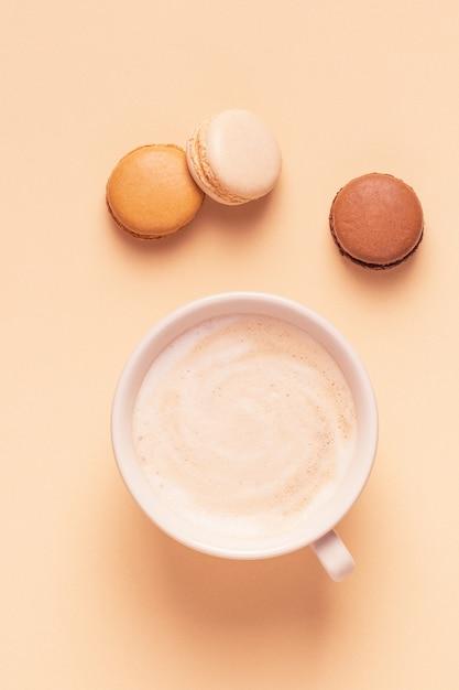 パステルカラーの背景にマカロンとコーヒーのカップ Premium写真