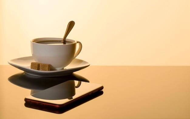 白いカップでエスプレッソのカップと反射とガラステーブルの上のスマートフォン Premium写真