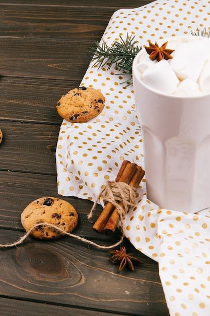スパイスとチョコレートクッキーで覆われた紙の上にホットチョコレートのスタンド 無料写真