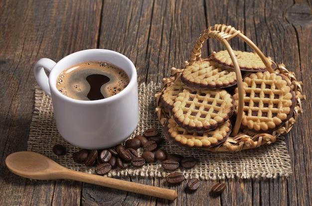 一杯のホットコーヒーとバスケットの丸いクッキー Premium写真
