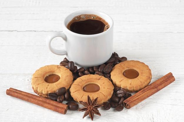 一杯のホットコーヒーとテーブルの上の甘いクッキー Premium写真