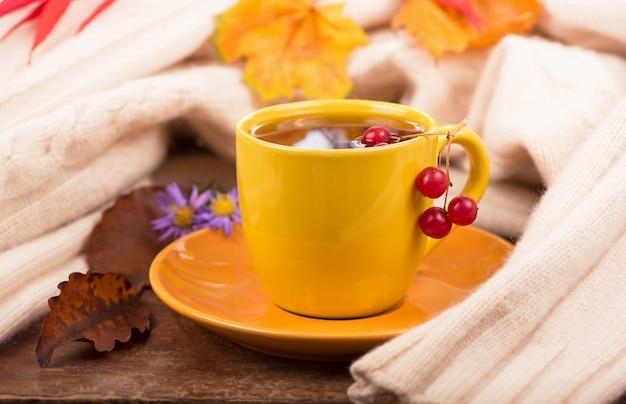 Чашка горячего чая и осенние листья, на коричневом фоне Premium Фотографии