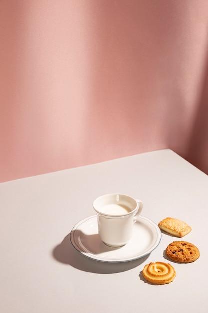 テーブルの上のさまざまなクッキーとミルクのカップ Premium写真