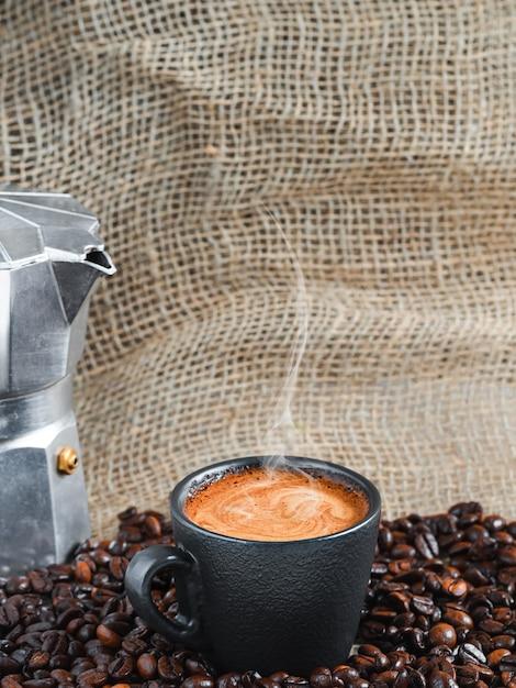 コーヒーポットの隣にある、焙煎したコーヒー豆の中に泡が入った強い芳香のエスプレッソコーヒーのカップ 無料写真