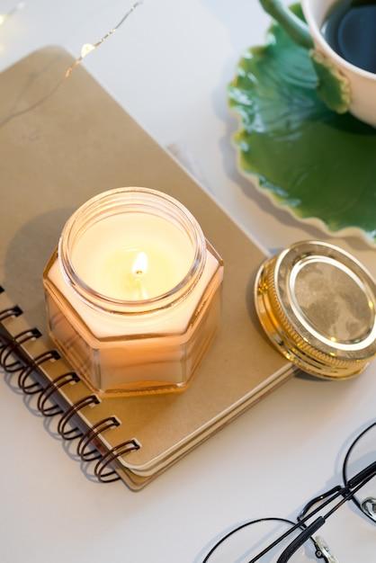 Чашка чая и ароматические свечи на тетради на белом столе Premium Фотографии