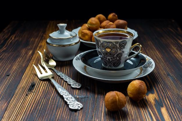 Чашка чая и пончики на деревянном столе Premium Фотографии