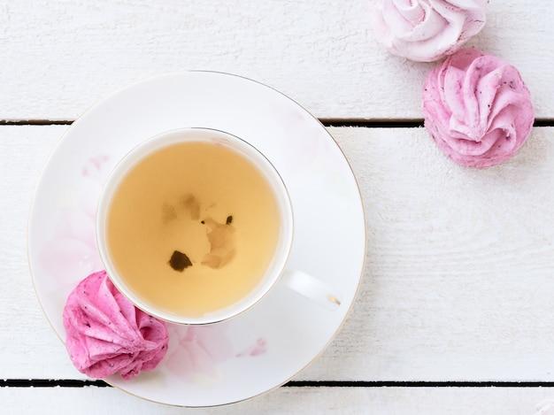 一杯のお茶とピンクのマシュマロと緑茶白。食物。菓子および飲料 Premium写真