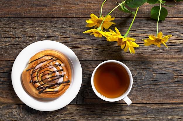 花と木製のテーブルの上のお茶と甘いパンのカップ Premium写真