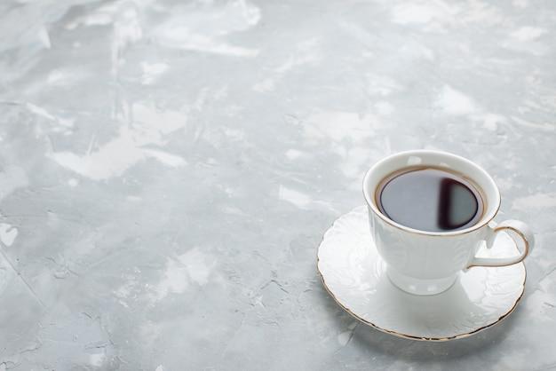 ライトデスクのガラスプレート上の白いカップの中に熱いお茶のカップ、甘いお茶を飲む 無料写真