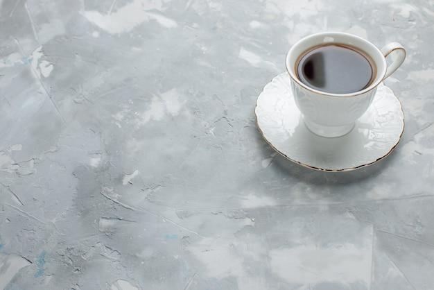 光の上のガラスプレート上の白いカップの中に熱いお茶のカップ、甘いお茶を飲む 無料写真