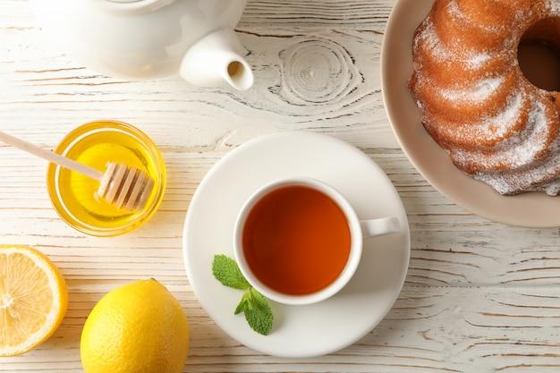 一杯のお茶、レモン、ミント、蜂蜜、ひしゃく、木製、上面のパイ Premium写真