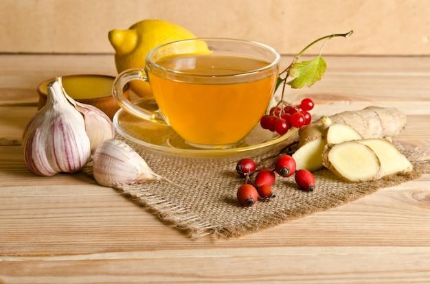 木製のテーブルにお茶、生姜、蜂蜜、ローズヒップベリー、ガマズミ属の木のスライス Premium写真