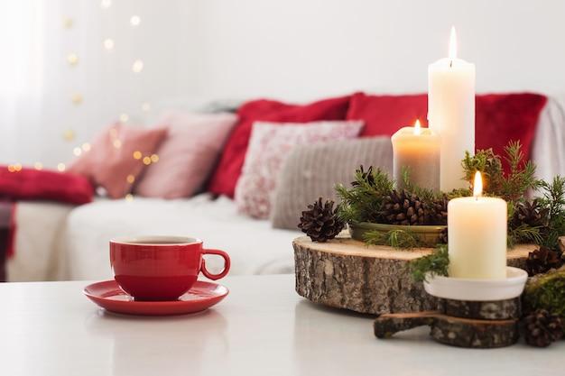 白いテーブルの上に燃えるろうそくとお茶のカップ Premium写真