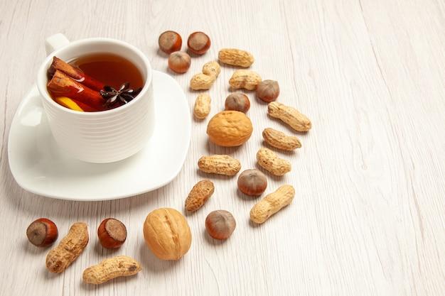 白の異なるナッツとお茶のカップ 無料写真