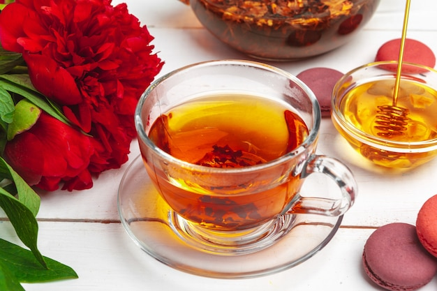 お菓子と木製のテーブルの上に花とお茶のカップ Premium写真