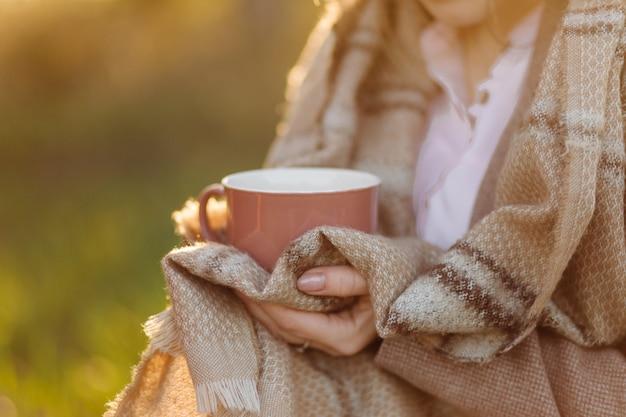 손에 일몰에 컵 어린 소녀는 담요로 덮여 무료 사진