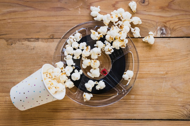 Cup of popcorn on top of cinema tape Free Photo