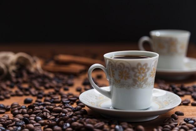 Tazza sul piattino vicino a chicchi di caffè Foto Gratuite
