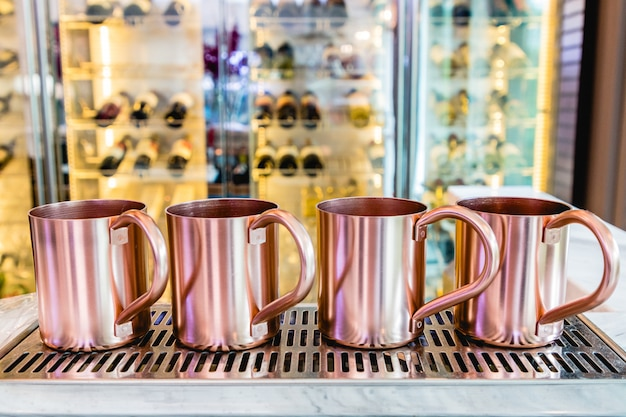 Cup stainless steel of copper or pink gold on a stainless tray. wine bar blurred. Premium Photo