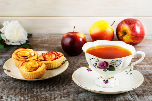 Cup of tea and apple rose shaped muffins Premium Photo