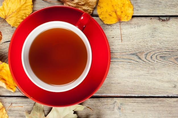Cup of tea and autumn leaves on table Premium Photo